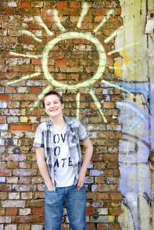 Germany, Berlin, Boy standing in front of brick wall with graffiti - MVC000016