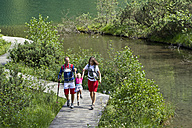 Germany, Bavaria, Chiemgau, Family walking at mountain lake - FF001368