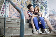 Germany, Berlin, Teenage boy and girl hugging, smiling - MVC000001
