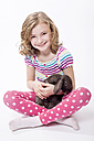 Portrait of girl sitting with bunny, smiling - STB000022