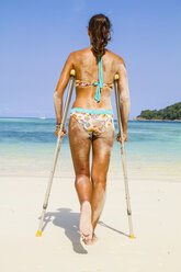 Thailand, Koh Surin island, woman with crutches standing at the white sandy beach - MBEF000727