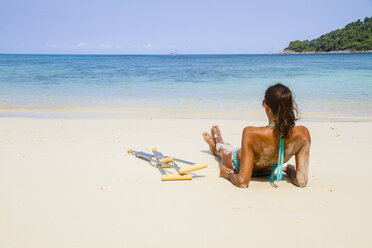 Thailand, Koh Surin island, woman with crutches lying at the white sandy beach - MBEF000724