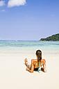 Thailand, Koh Surin island, woman lying at white sandy beach - MBEF000721
