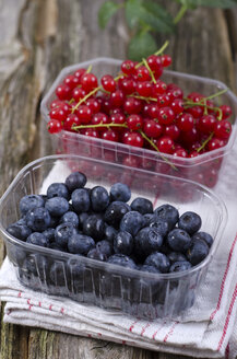 Red currants with blueberries and napkin on wooden table, close up - OD000344
