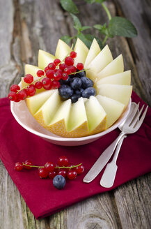 Bowl of honeydew melon with red currant and blueberries on wooden table, close up - OD000348