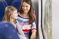 Germany, Brandenburg, Mother with daughter traveling through train - KFF000213