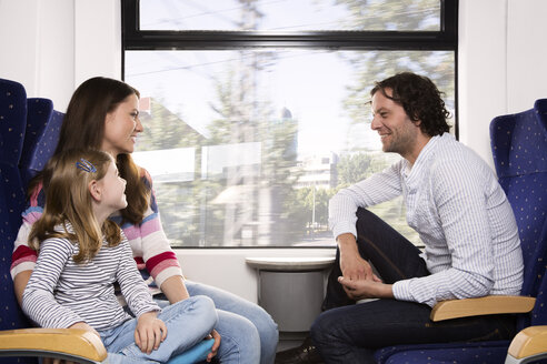 Germany, Brandenburg, Family traveling in train, smiling - KFF000215