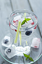 Glass of mineral water with ice cubes and frozen berries on wooden table, close up - ODF000365