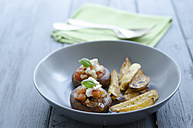 Bowl of mushrooms with roasted potatoes and napkin on wooden table, close up - OD000378