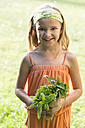 Germany, Bavaria, Portrait of girl holding bunch of herbs, smiling - STB000049