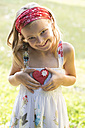 Germany, Bavaria, Girl holding heart shaped biscuit, smiling - STB000045