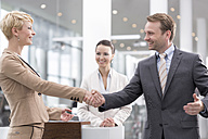 At the car dealer, Happy man and woman shaking hands - MLF000061