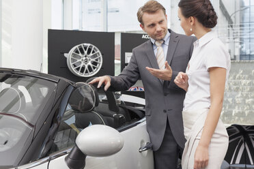 At the car dealer, Salesman talking to client at convertible car - MLF000012