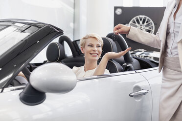 At the car dealer, Woman in convertible receiving car keys - MLF000067
