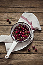 Fresh sour cherries in a colander on a wooden table - CZF000073
