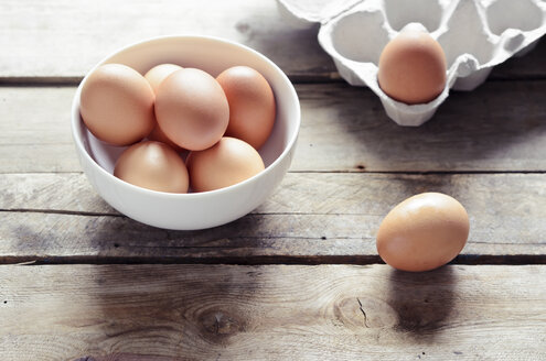 Studio, brown eggs in a bowl on a wooden table - CZ000072