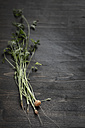 Fresh baby carrots with stems and leaves on wooden board - SBD000196