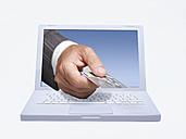 Manager hand giving a credit card through lap top screen, digital composite - BSCF000364
