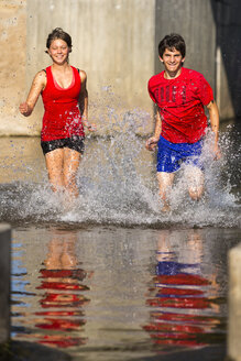 Germany, Baden-Wuerttemberg, Winterbach, athletic young man and young woman running through Rems river - STSF000115