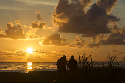 Germany, Lower Saxony, Wremen,  Couple watching sunset at North Sea - SJ000055