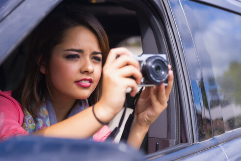 Teenage girl taking picture out of car - ABAF000997