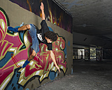 Germany, Stuttgart, Hall of Fame, Hip Hop dancer at airbrush wall - STSF000139
