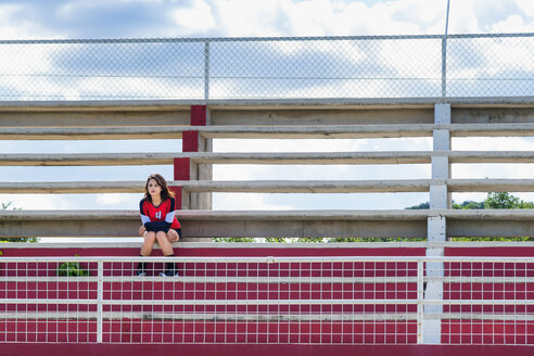 USA, Texas, American High School Girl in Sports Outfit sitting all alone on stadium bleachers - ABAF001004
