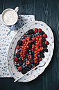 Berries on serving plate with cup of yoghurt - EC000307