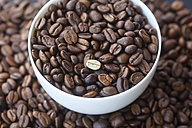 Roasted coffee beans and one unroasted in a bowl - JT000499