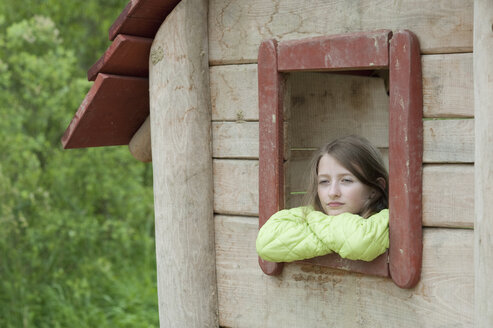 Germany, Bavaria, girl looking outside of the window of a wendy house - CRF002488
