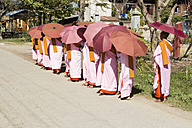 Myanmar, Bagan, Group of nuns with sunshades on road - DR000168