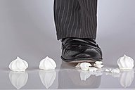 Shoe of businessman stepping on meringues - DRF000194