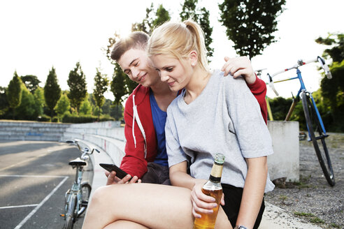Young couple with smart phone and beer bottle - FEXF000045