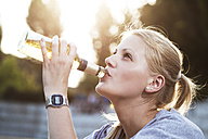 Young woman drinking beer of a bottle - FEXF000030