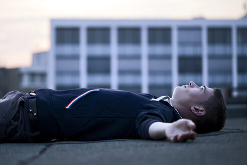 Young man lying on flat roof - FEXF000017