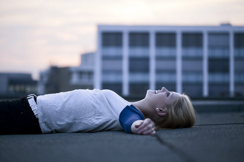 Young woman lying on flat roof - FEXF000014