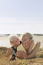 France, Bretagne, Landeda, Mother and daughter lying at the coast - LAF000122