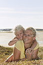 France, Bretagne, Landeda, Mother and daughter lying at the coast - LAF000124