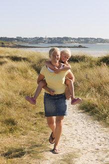 France, Bretagne, Landeda, Mother and daughter walking on dune - LAF000127
