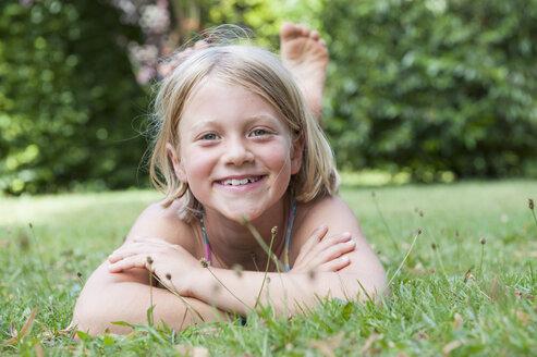 Smiling girl lying in grass - NHF001420