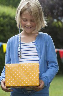 Girl holding birthday present - NHF001440
