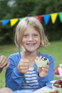 Happy girl eating muffin on a birthday party - NHF001448