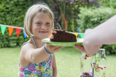Girl receiving piece of cake on a birthday party - NHF001451