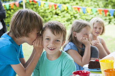 Two boys whispering on a birthday party - NHF001454