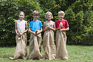 Four children standing in sacks side by side - NHF001460