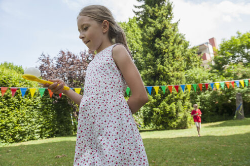 Children having a spoon and egg race in garden on a birthday party - NHF001459