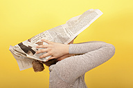 Young woman covering her face with newspaper - DRF000207