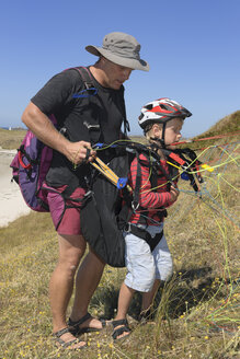France, Bretagne, Landeda, Father and son with paraglider in dune - LAF000156