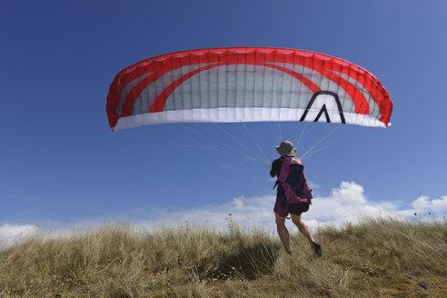 France, Bretagne, Landeda, Man paragliding - LAF000171