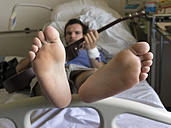 Young man playing guitar in hospital bed - LA000131